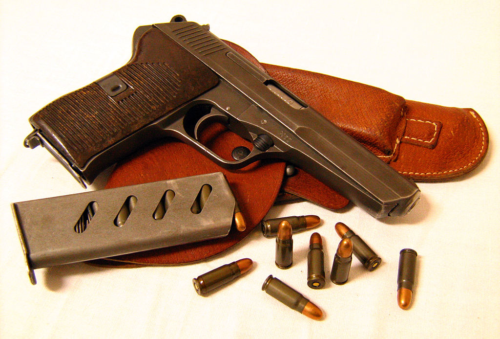 A picture of a Tokarev pistol with magazine, bullets and leather holster