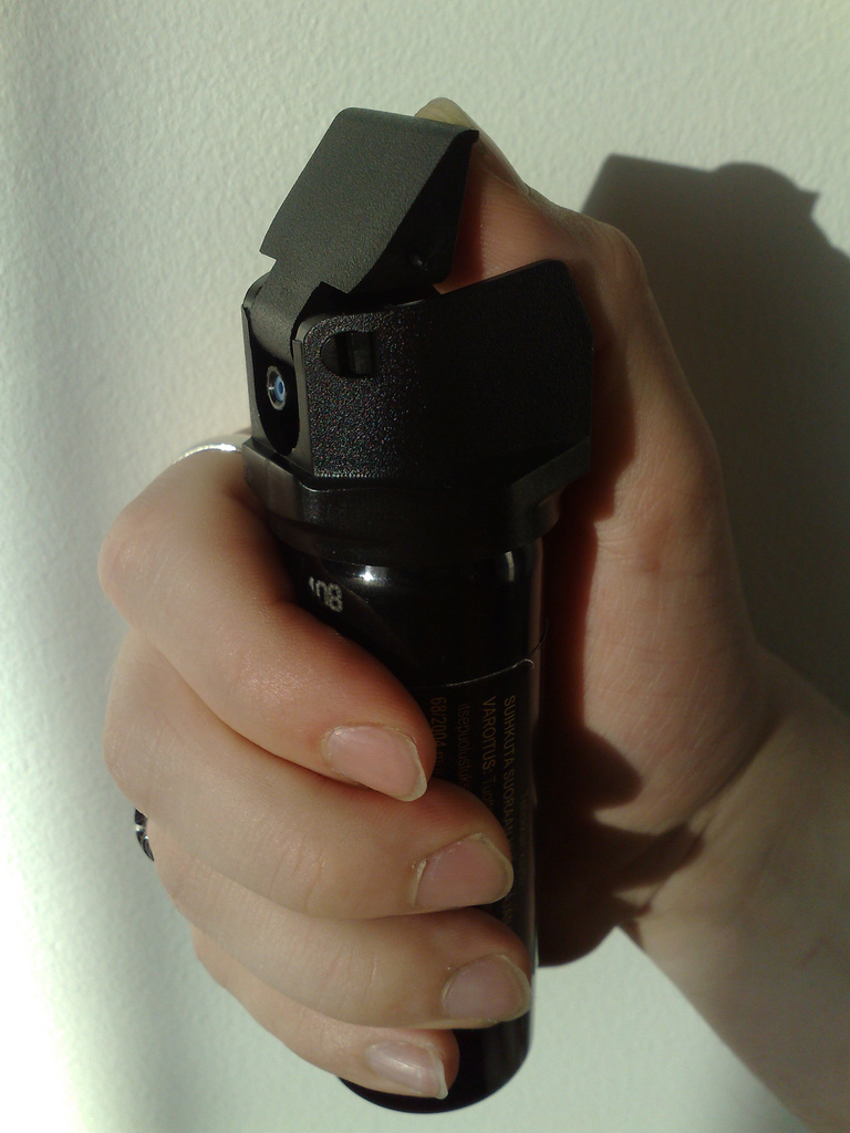 hand holding a black canister of pepper spray
