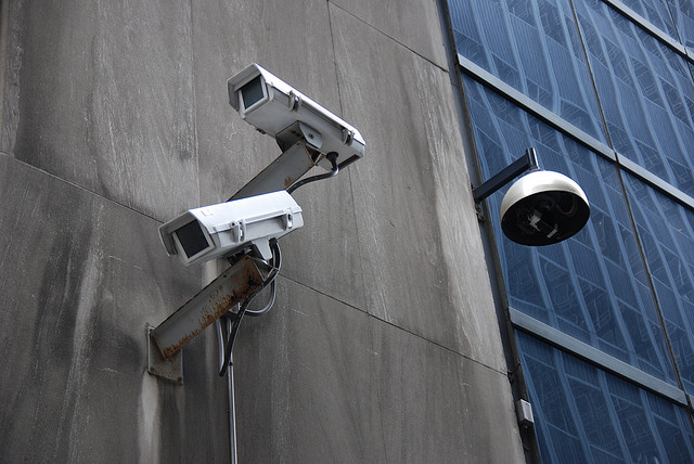 Surveillance cameras mounted on the side of building.